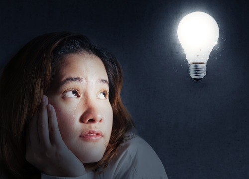 Portrait of a woman looking a light bulb